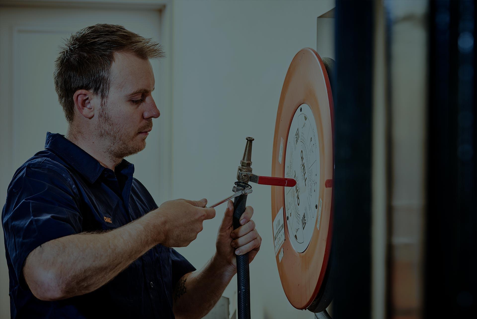 An Alexon employee installing a fire hose.