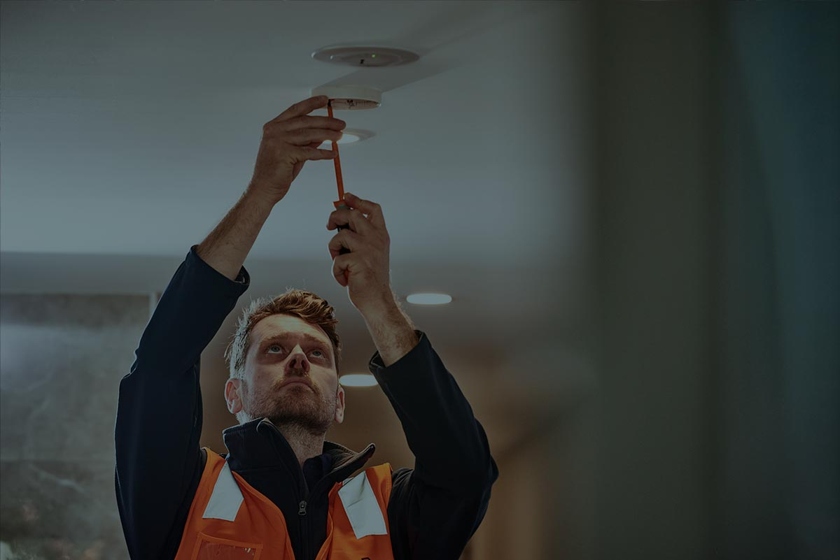An Alexon employee unscrewing a smoke alarm for a routine inspection.