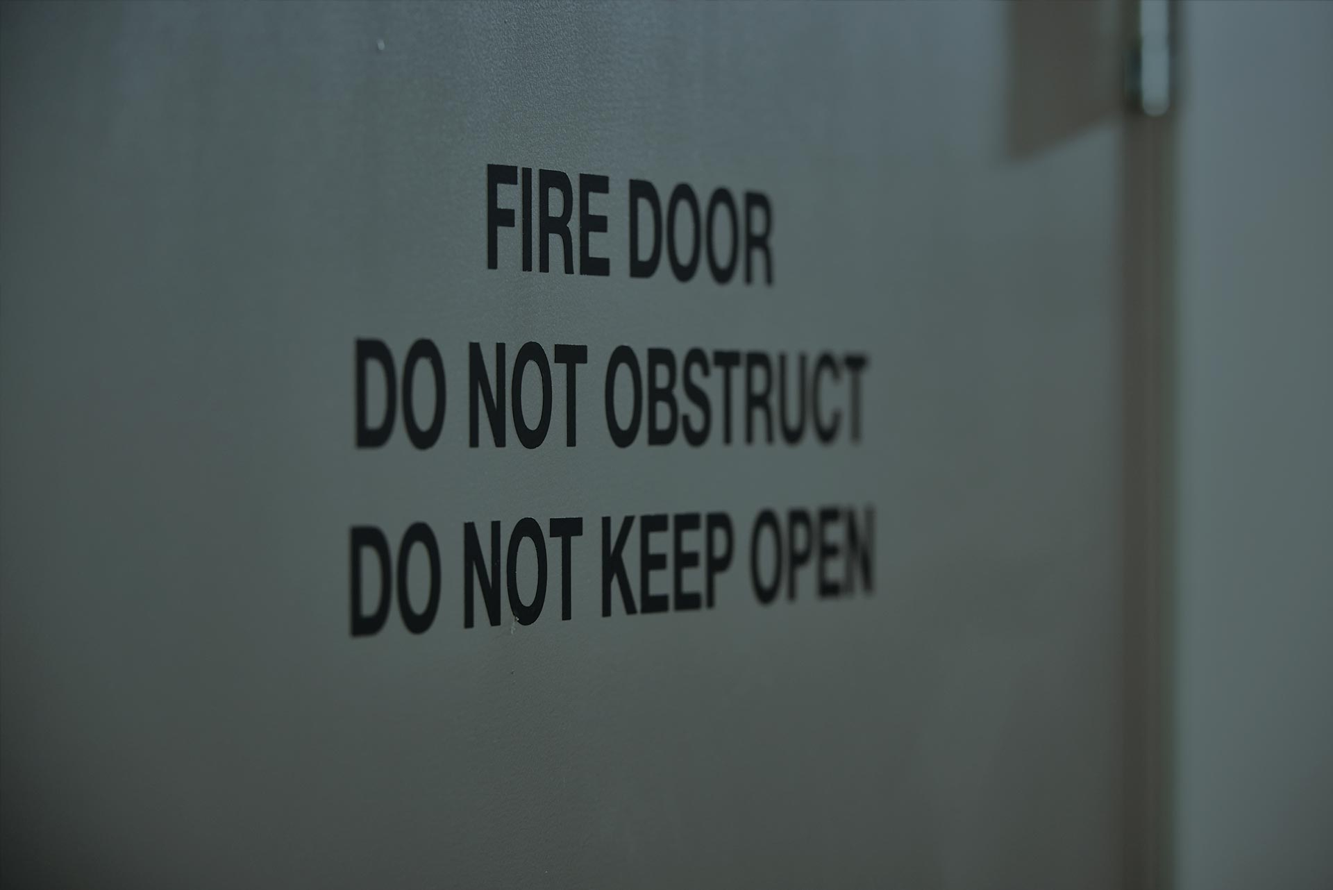 "A photo of the words: ""Fire Door"" ""DO NOT OBSTRUCT"" ""KEEP OPEN""."