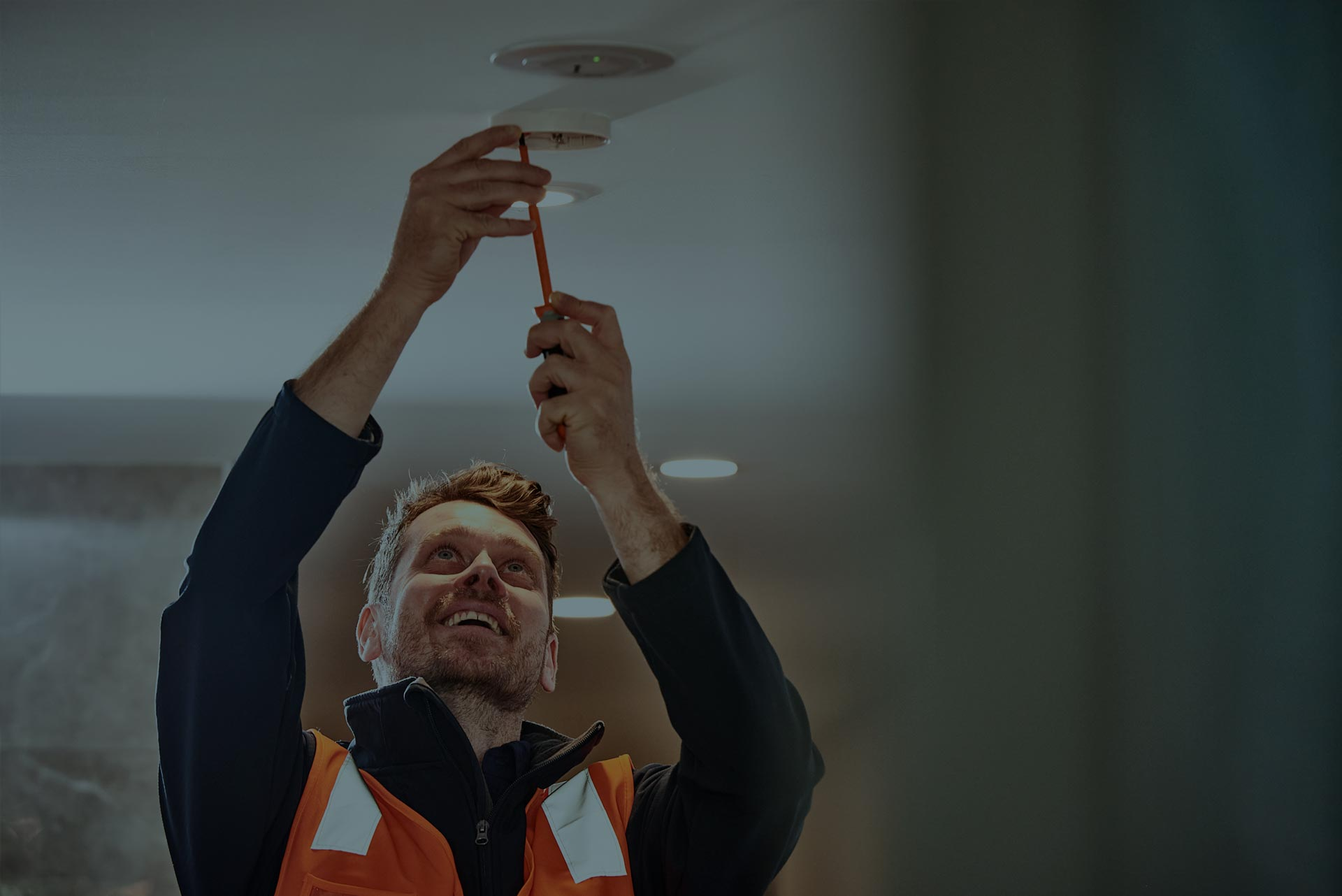 An Alexon employee unscrewing a smoke alarm to perform a routine inspection.