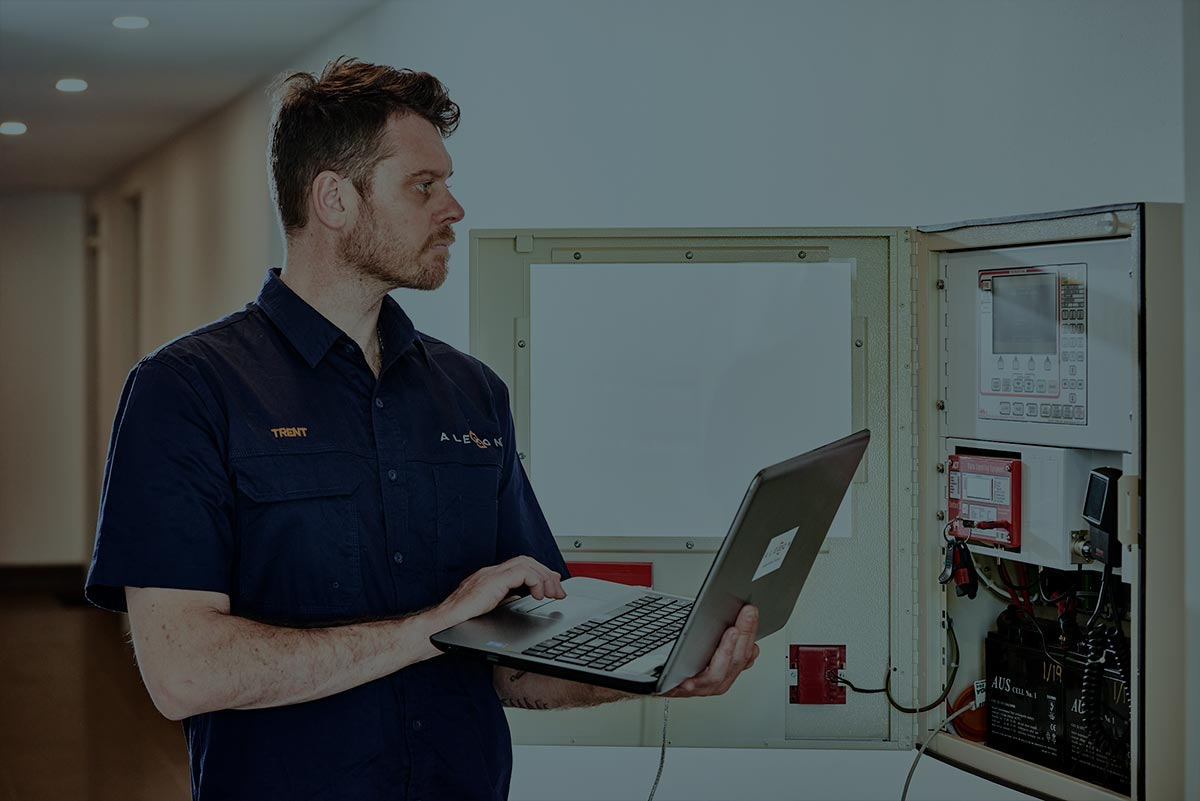 An Alexon electrician performing systems checks on a control panel.