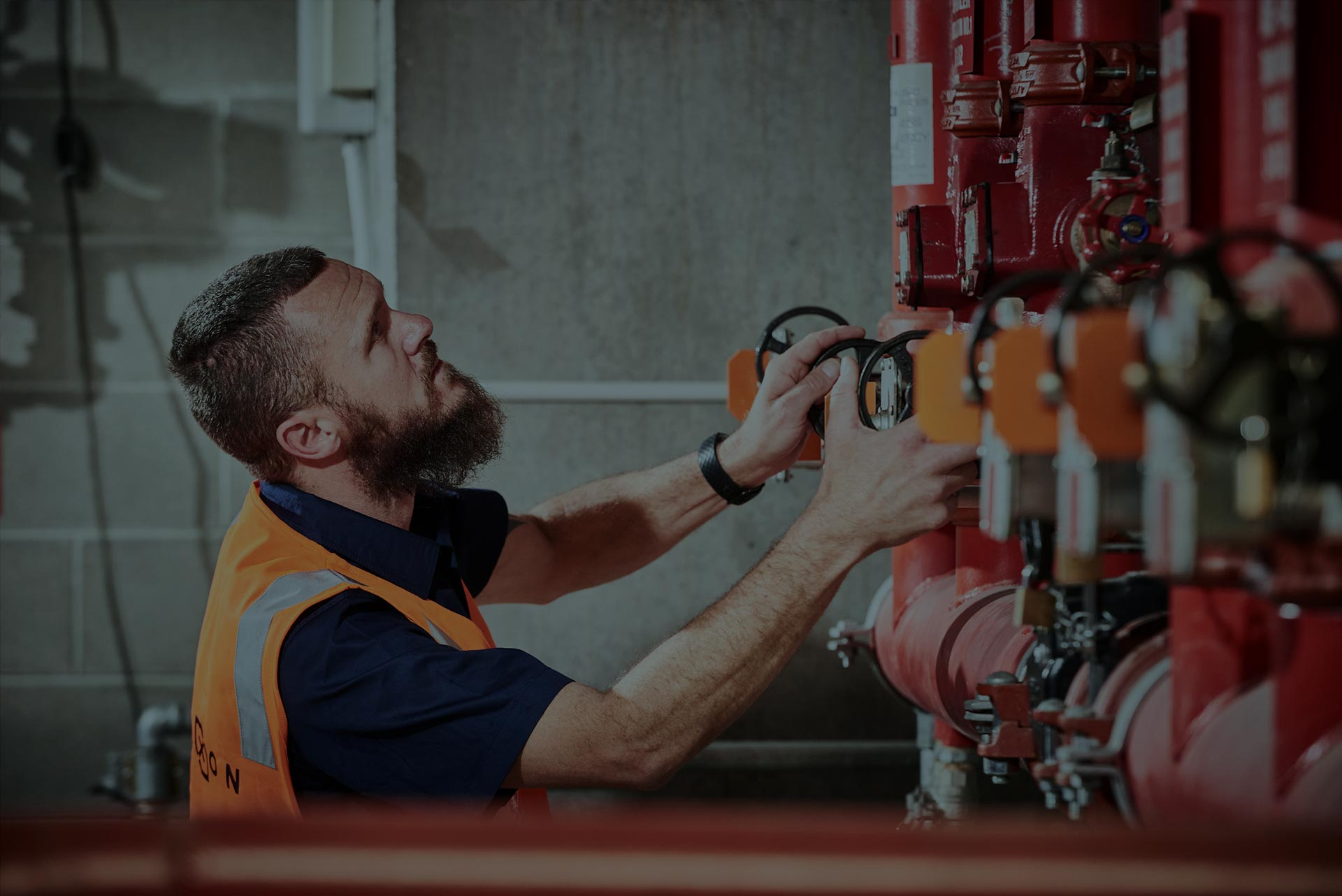 An Alexon employee performing maintenance checks on some fire equipment pipes.