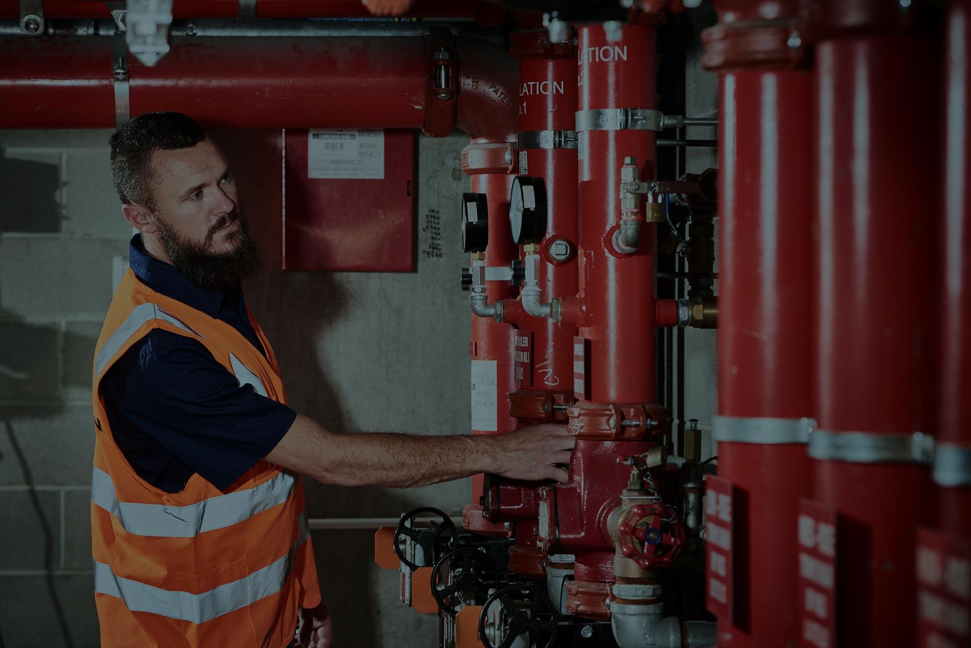 An Alexon employee performing maintenance on some fire equipment.