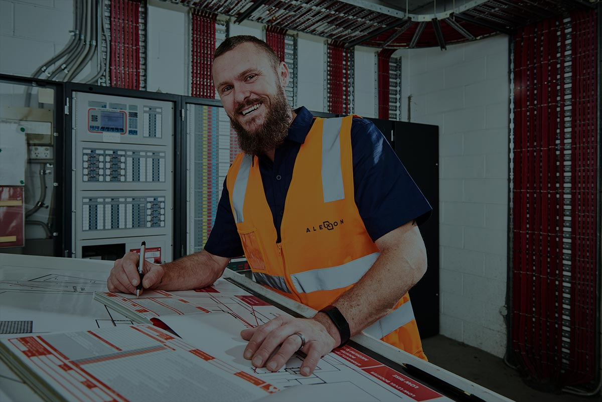 Alexon employee smiling at the camera while completing maintenance reports.
