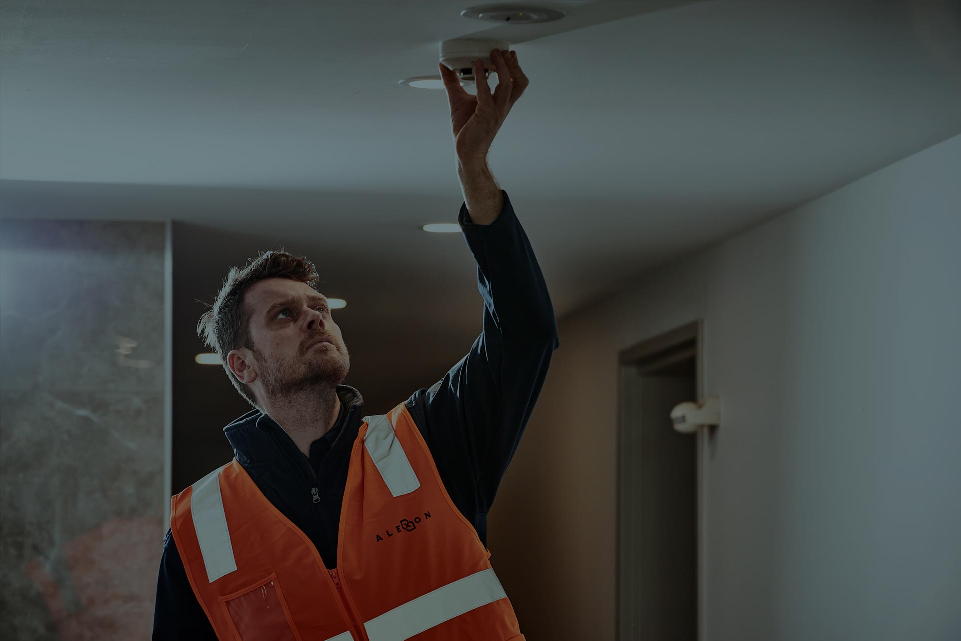 Alexon employee in a safety vest replacing smoke detectors in an apartment complex.