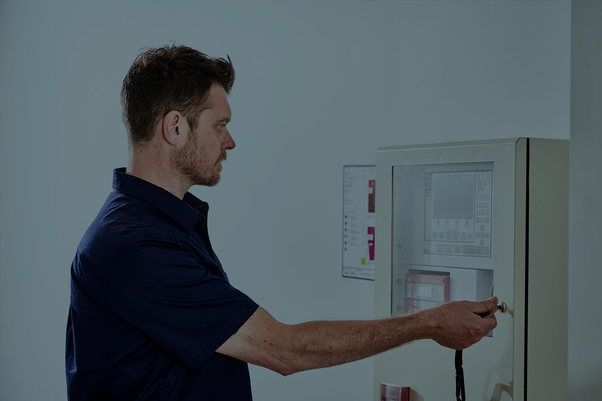 An Alexon employee closing and locking a fire systems control panel.