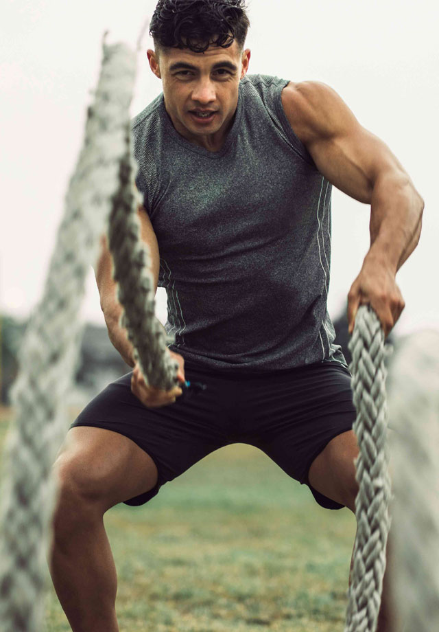 Man working out with battle ropes for fitness