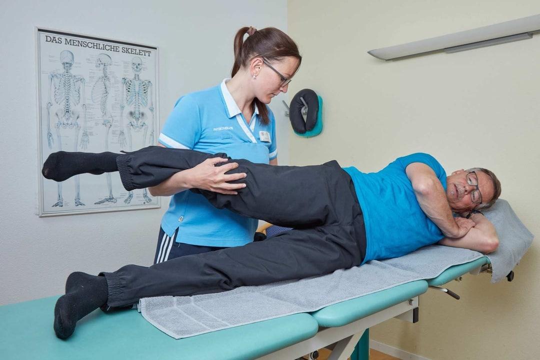 Physiotherapeutin bewegt Bein eines liegenden Patienten