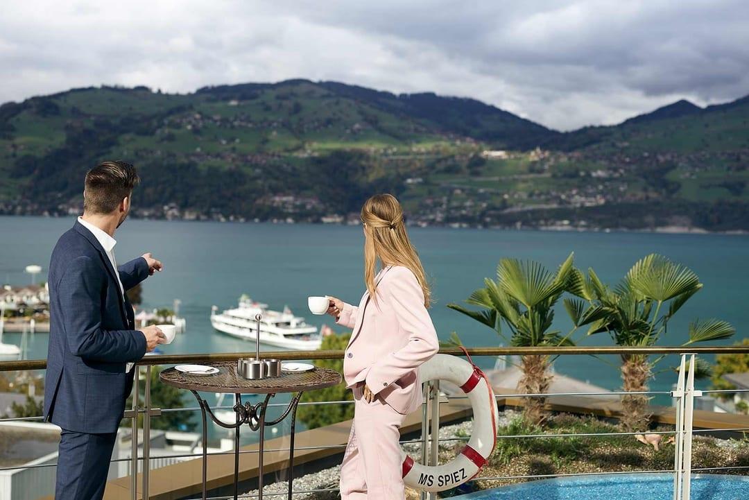 Mann und Frau blicken von Terrasse auf den Thunersee