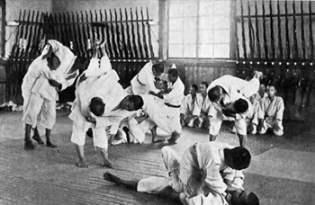 Vintage judo lesson with multiple pairs executing throws on the mat.