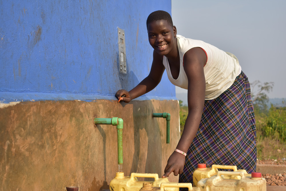 Fatuma fills a jerry can with water from the Water Compass water point and smiles at the camera