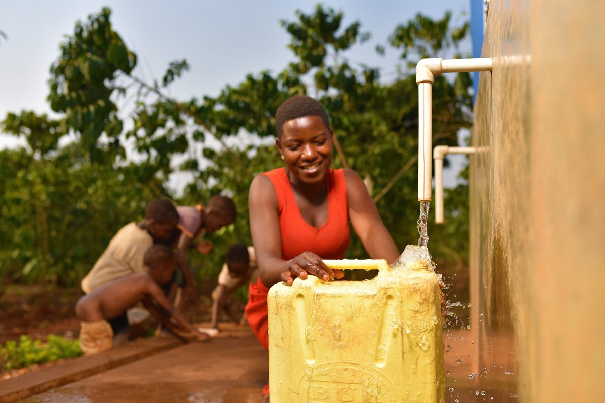 A young woman filling up a jerry can with water from a water point