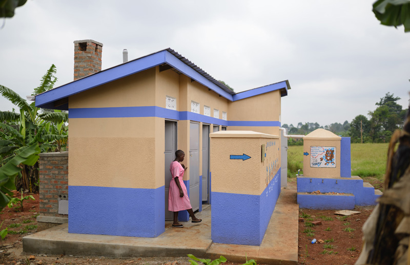 A teenaged girl walking out of a new toilet facility on her school's campus
