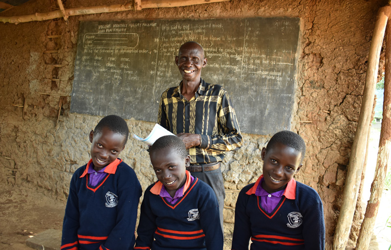 A teacher stands behind three of his students in a clay-walled classroom