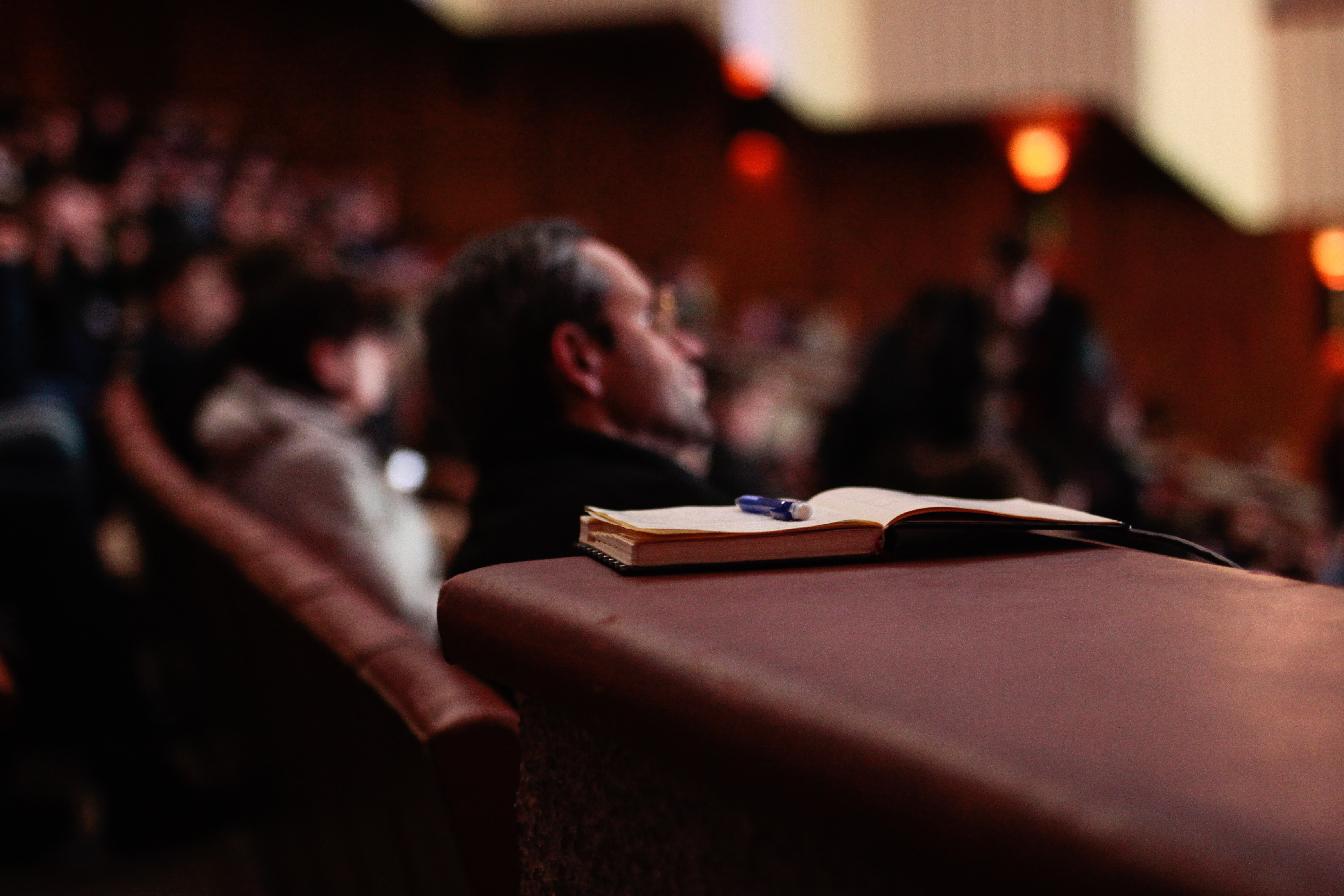 Advocate: Open notebook with a pen in an auditorium with people