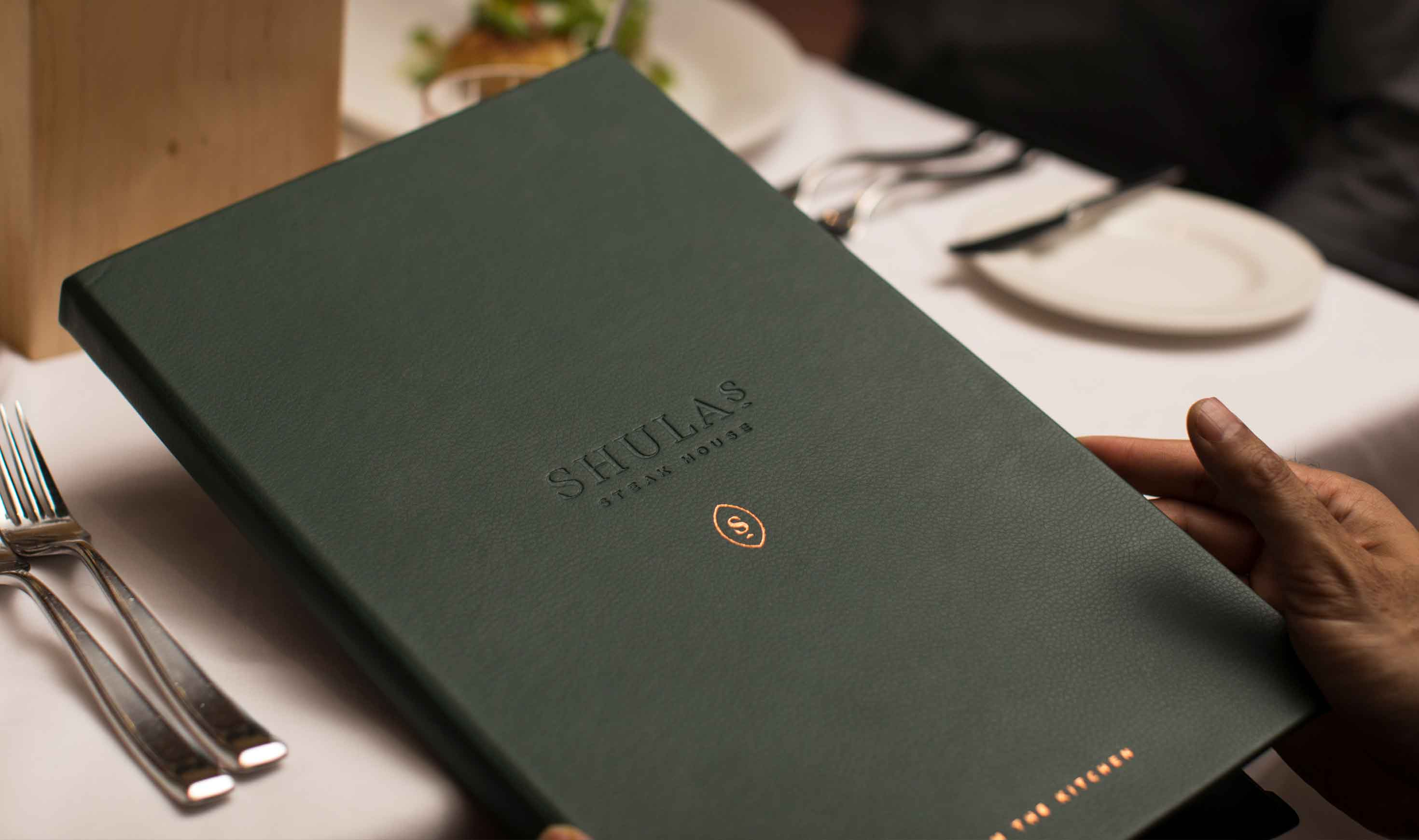 Man at restaurant table holding Shula's Steak House menu, showing debossed, foil-stamped cover
