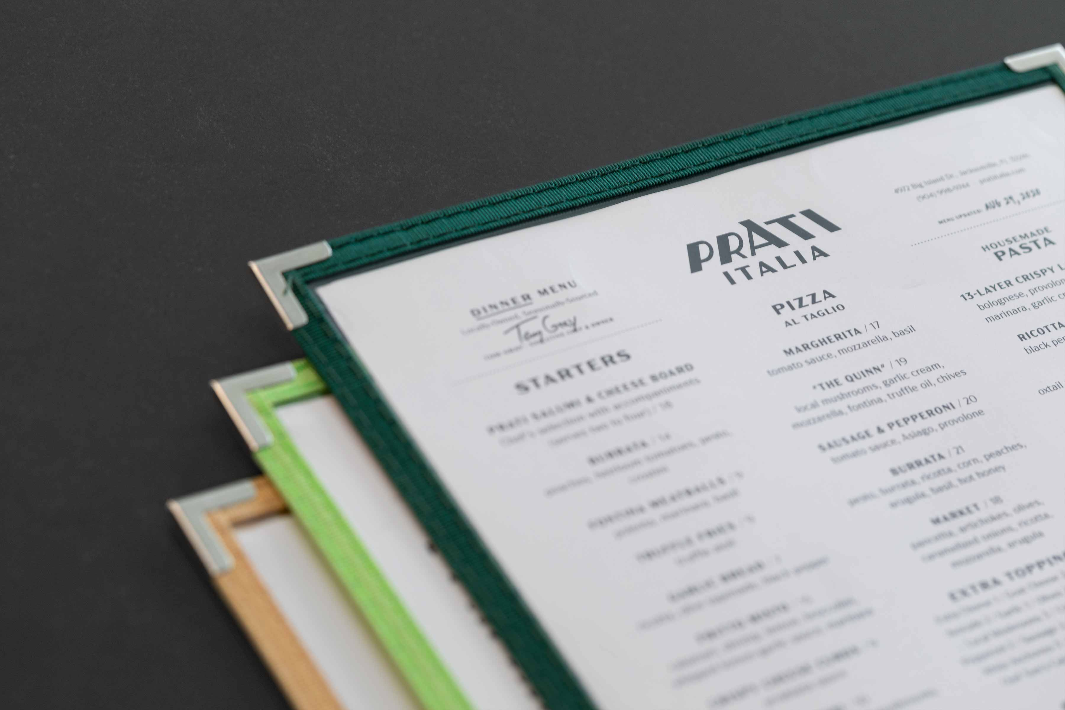 Close-up photo of 3 different colored menu covers for Prati Italia