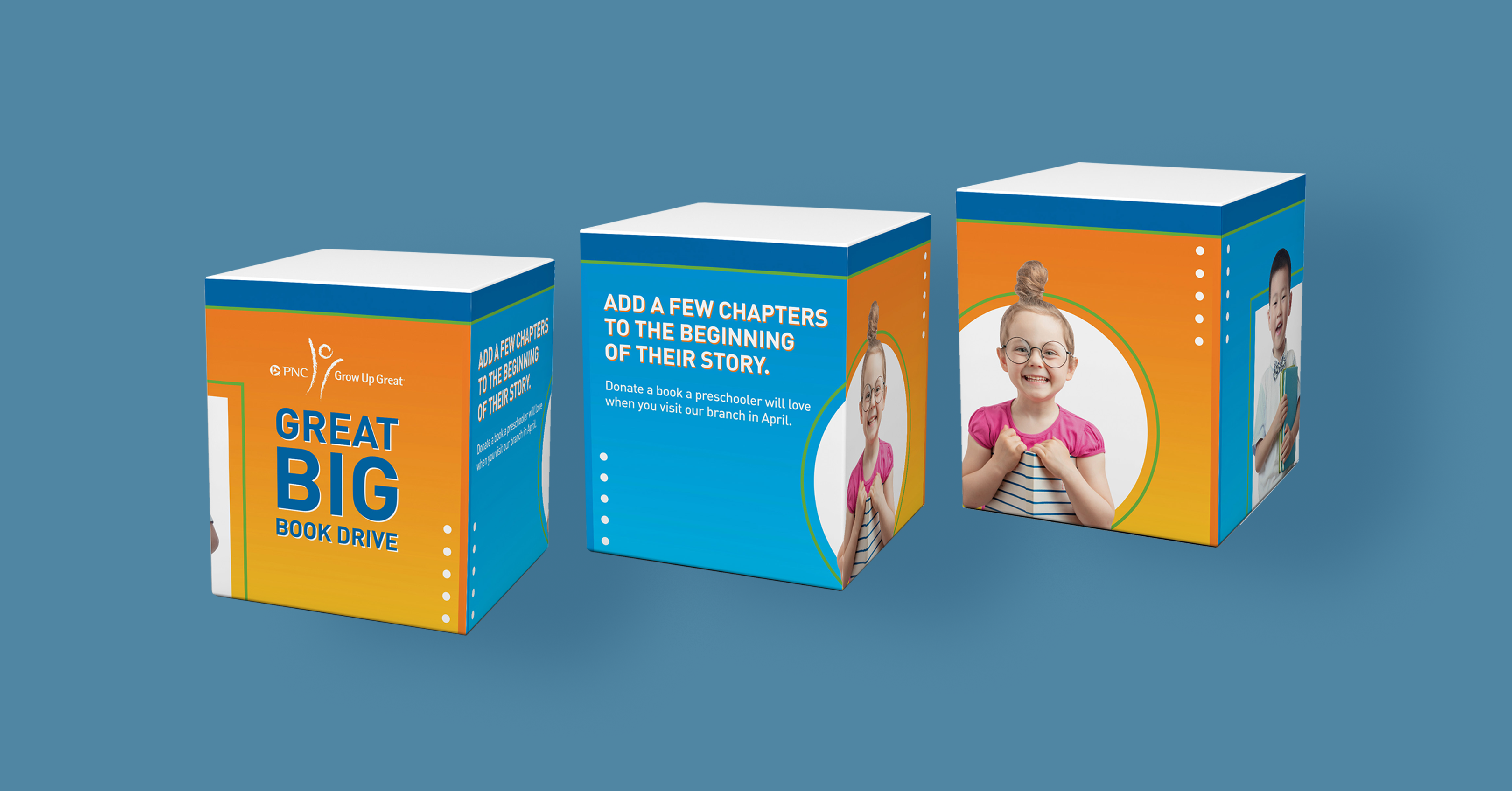 """A mockup of a cube-shaped box from three different angles, over a blue background. The sides of the box alternate from a yellow-orange gradient to a teal-blue gradient. The main side features copy that reads """"Great Big Book Drive,"""" and two of the sides features images of children holding books and smiling, overlaid on white shapes. The top of the box has a thick, dark blue border."""