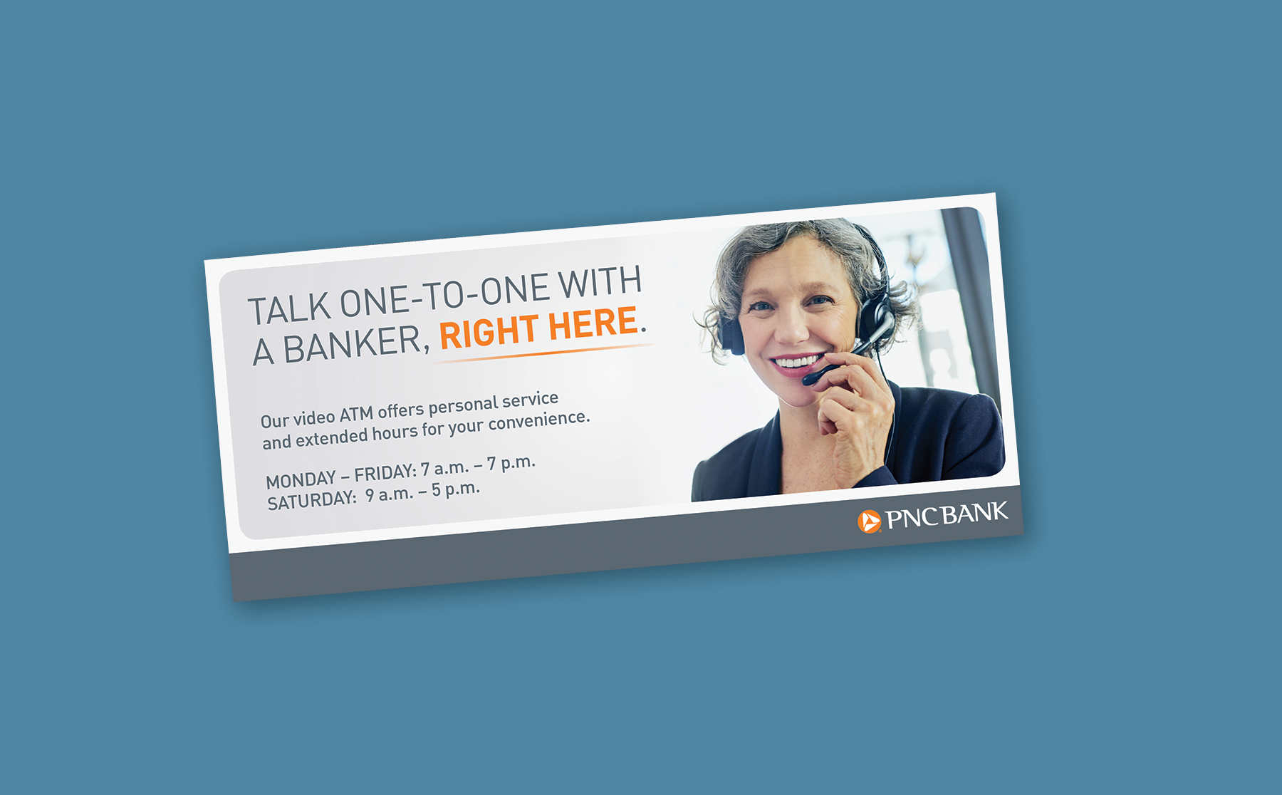 """A mockup of a long, horizontal sign over a blue background. The sign features a light gray gradient background, with a headline reading """"Talk one-to-one with a banker, right here"""" next to an image of a happy banker speaking through a headset."""