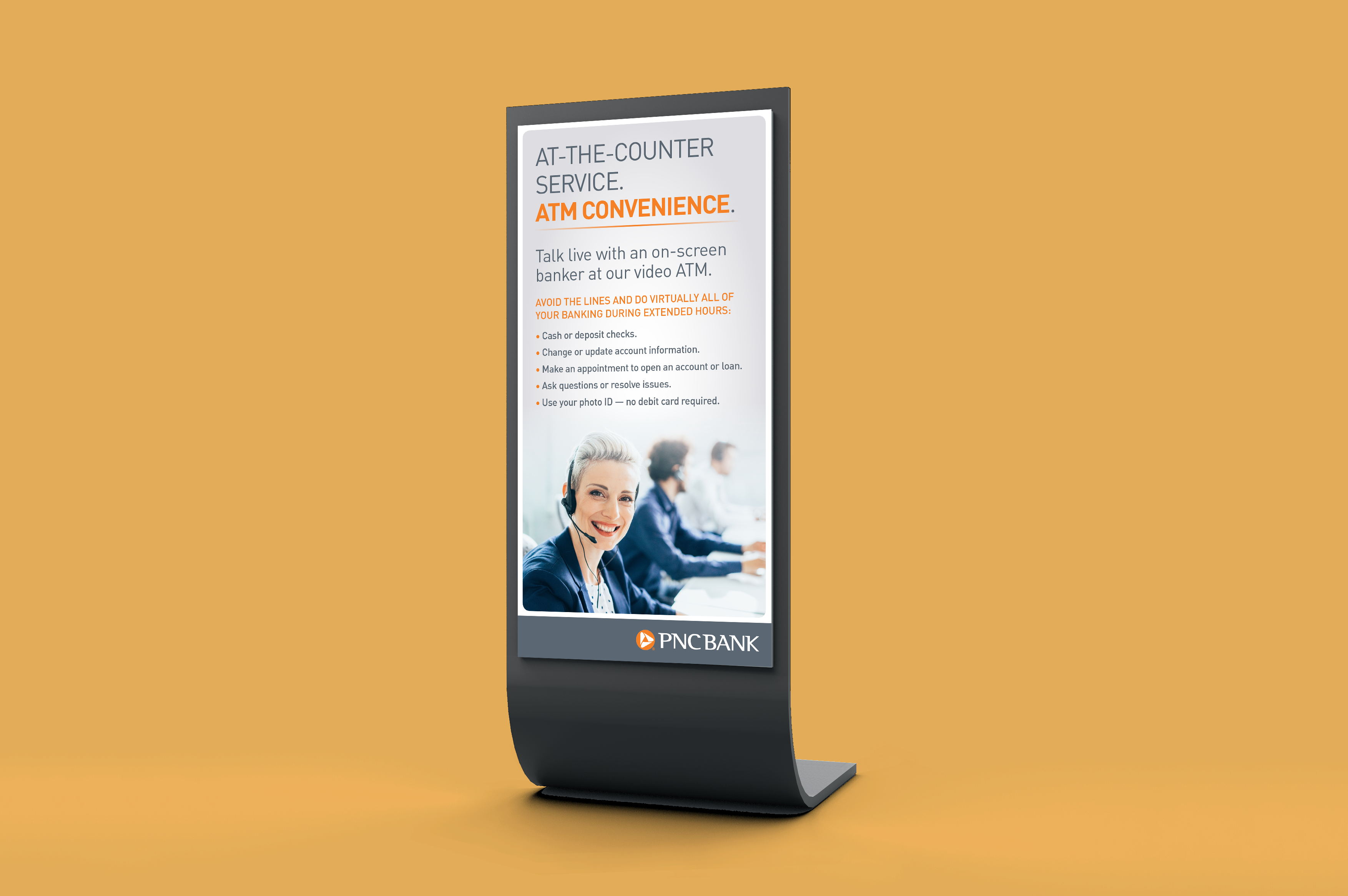 """A mockup of a tall, vertical sign over a mustard background. The sign features a light gray gradient background, with a headline reading """"At the counter service. ATM convenience"""" above an image of a happy banker speaking through a headset."""