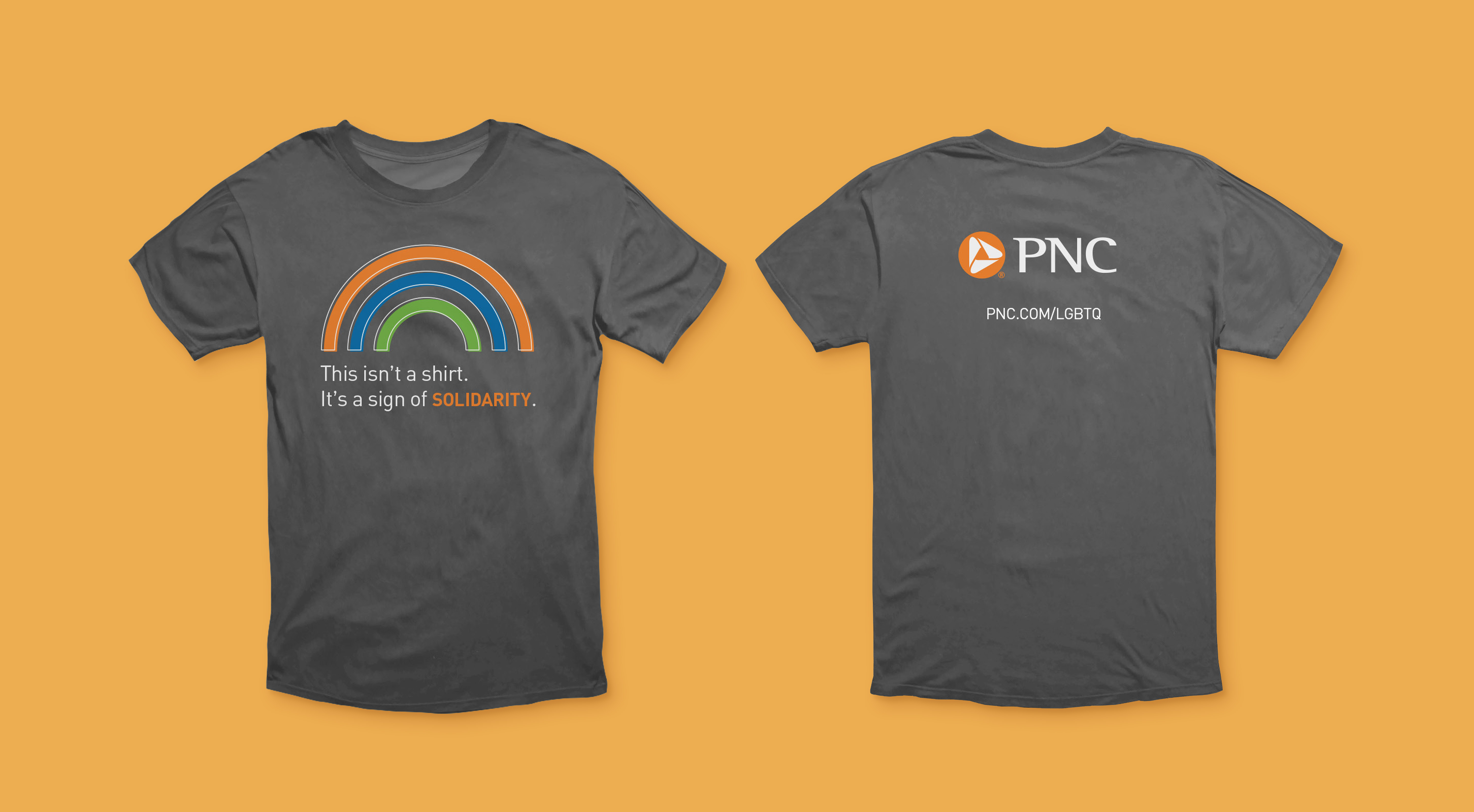 """A mockup of the front and back of a dark gray t-shirt over a mustard background. The front features an orange, blue, and green rainbow graphic and text that reads """"This is not a shirt. It's a sign of solidarity."""" The back features the PNC logo and a URL reading """"pnc.com/LGBTQ."""""""