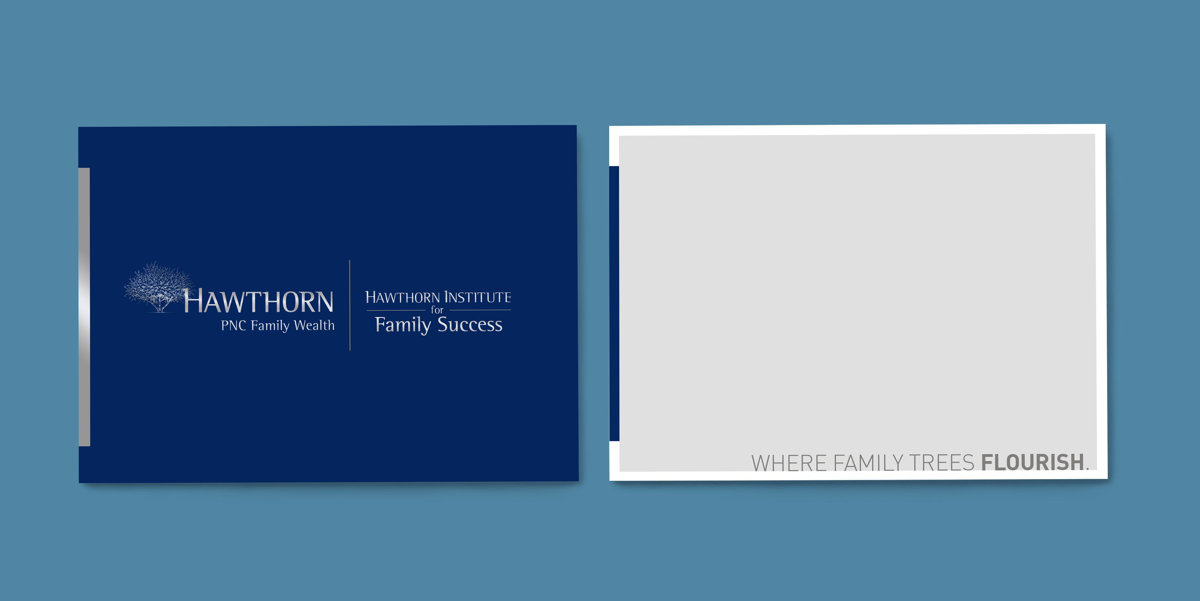 """A mockup of the front and back of a notecard over a blue background. The front of the card is dark blue with a vertical bar on the left in silver foil. The Hawthorn Institute for Family Success logo lockup is in the center of the card, also in silver foil. On the back, there is a light gray background with a  white border and the same vertical bar on the lefthand side - but this time, in dark blue. The tagline """"Where family trees flourish"""" is written in dark gray in the bottom righthand corner."""