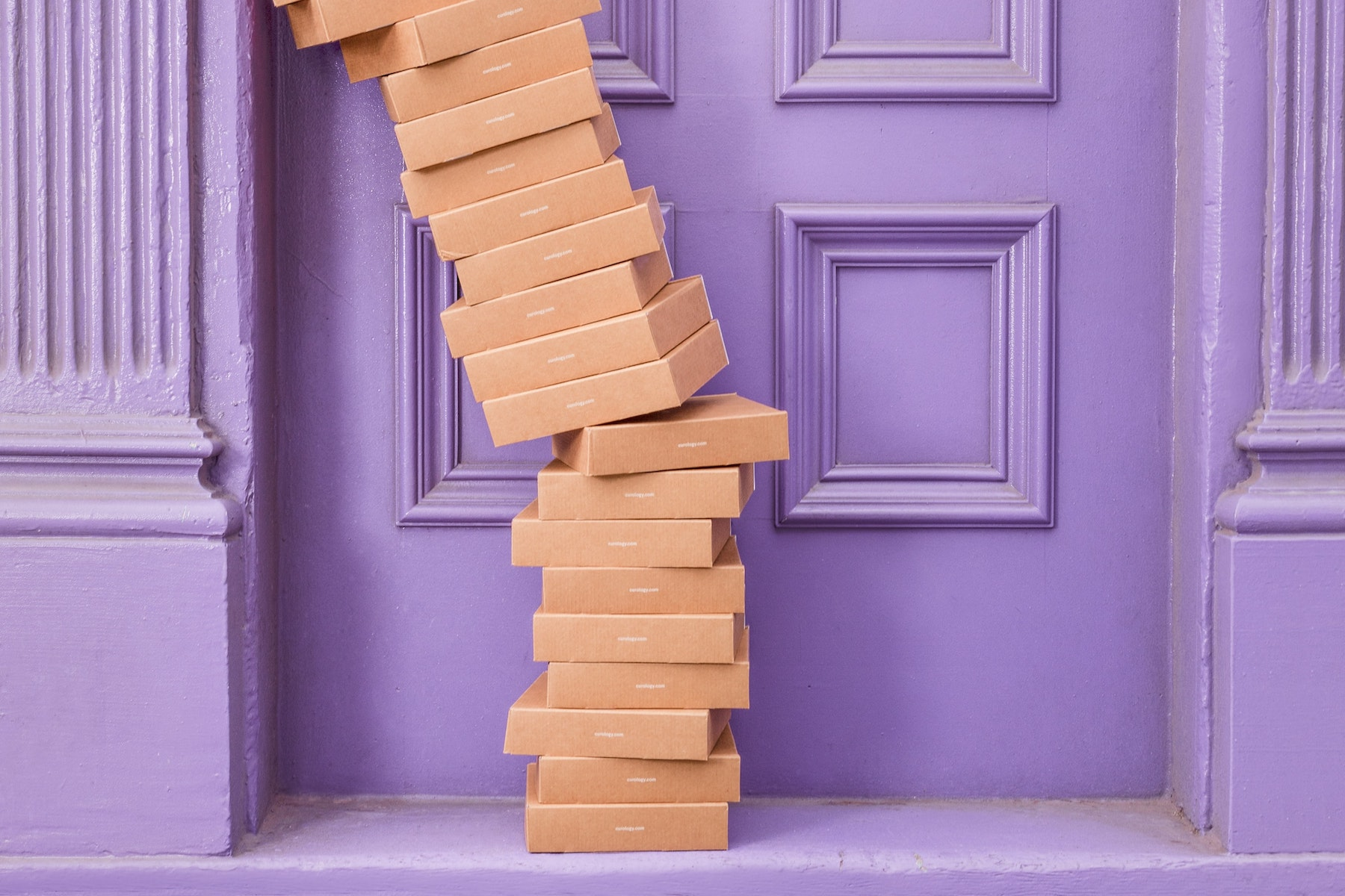 stack of fashion ecommerce boxes outside a front door