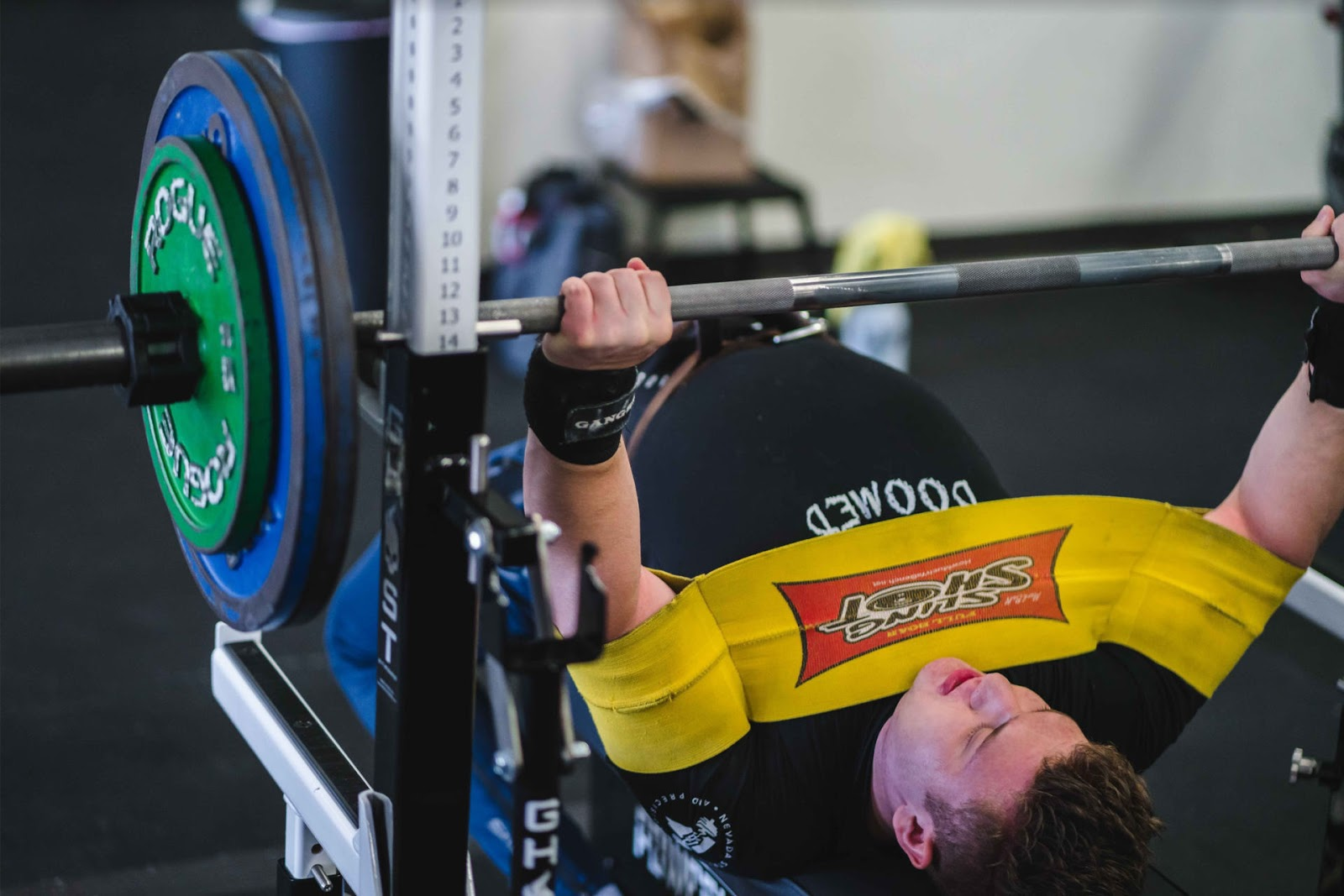 man bench pressing with yellow tension band