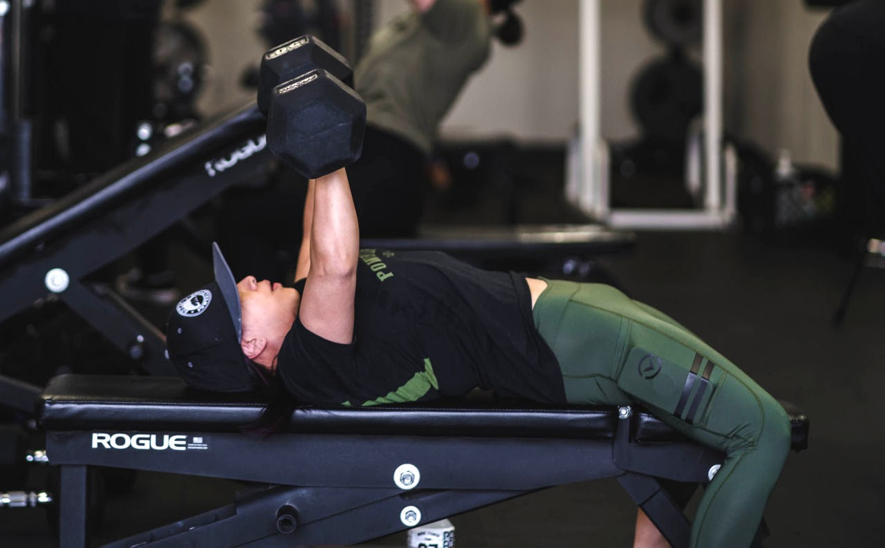 woman with green leggings performing dumbbell benchpress
