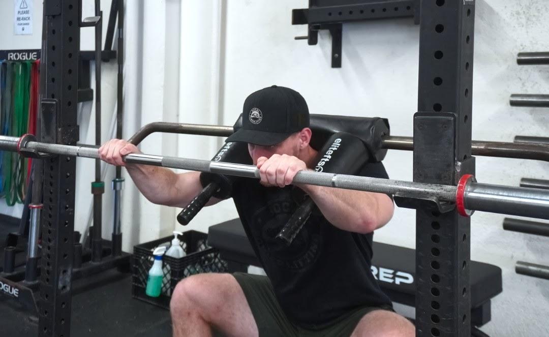 man performing hatfield squat wearing socal powerlifting hat