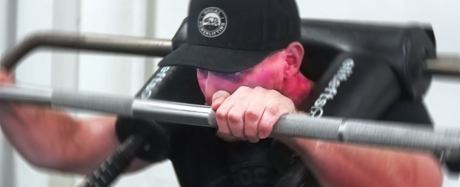 close up to man's face while squatting. his face is comically red from exertion.