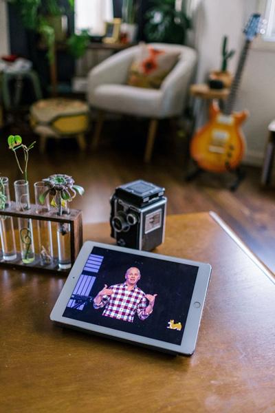Tablet on a desk with Pastor Ben speaking during Epic online service.