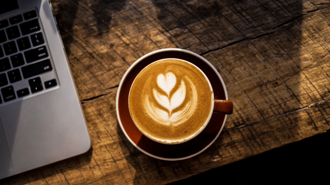 Cup of coffee with a laptop on wood table