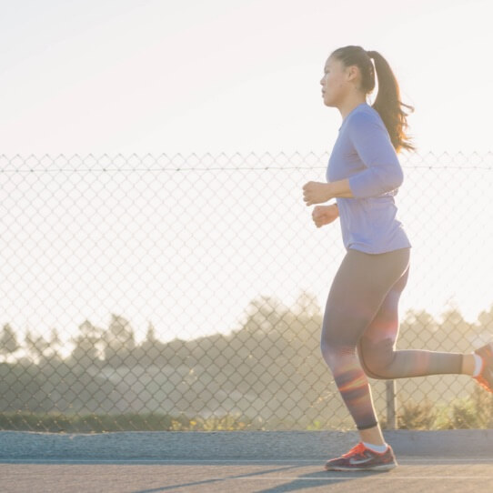 Woman running along outdoor track