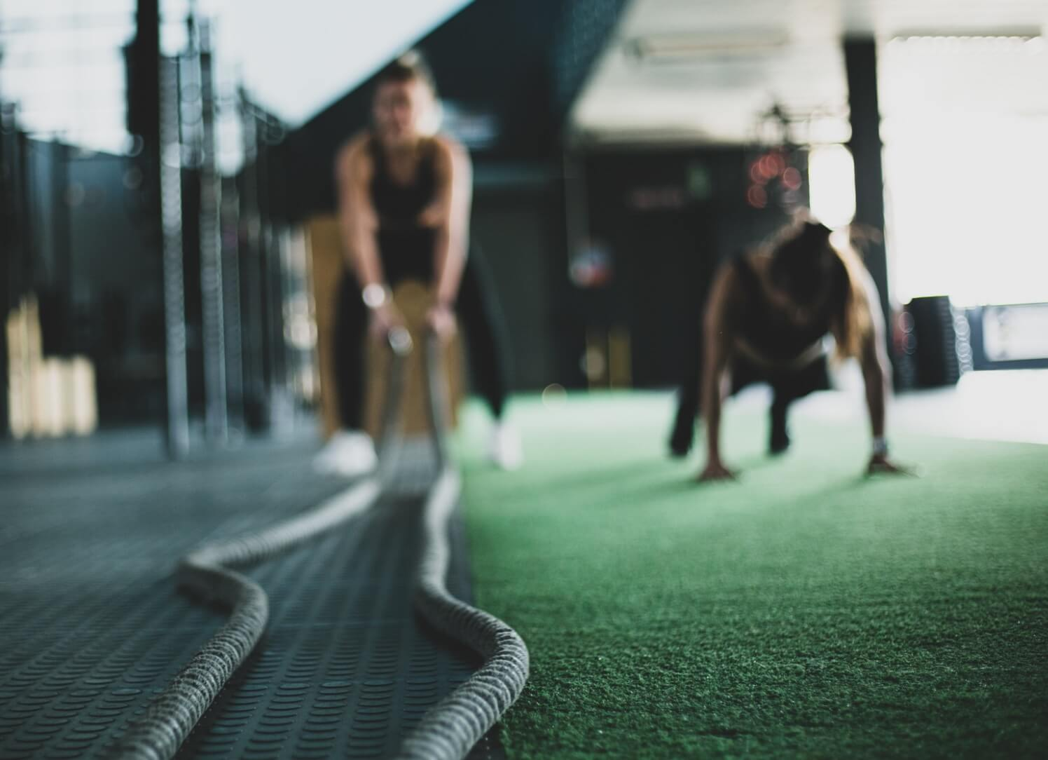 Two women doing gym workout, push ups and battle ropes