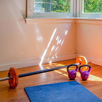 Room with gym equipment and yoga matt