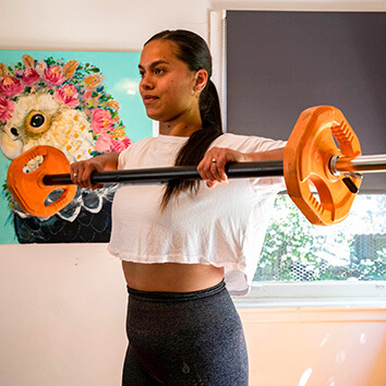 Woman doing exercise at home, lifting weights