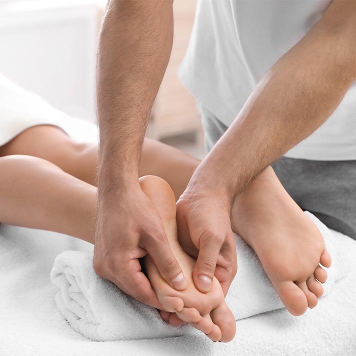 Woman receiving reflexology, foot massage