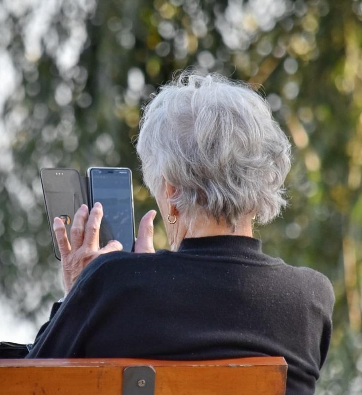 Vrouw zoekt op telefoon in het park