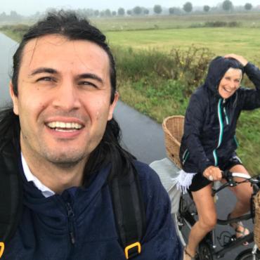 Twee mensen lachen op de fiets door weer en wind