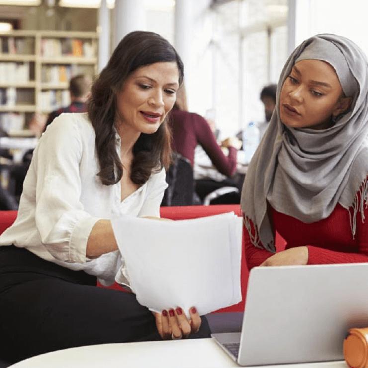 Een vrouw helpt een andere vrouw met formulieren