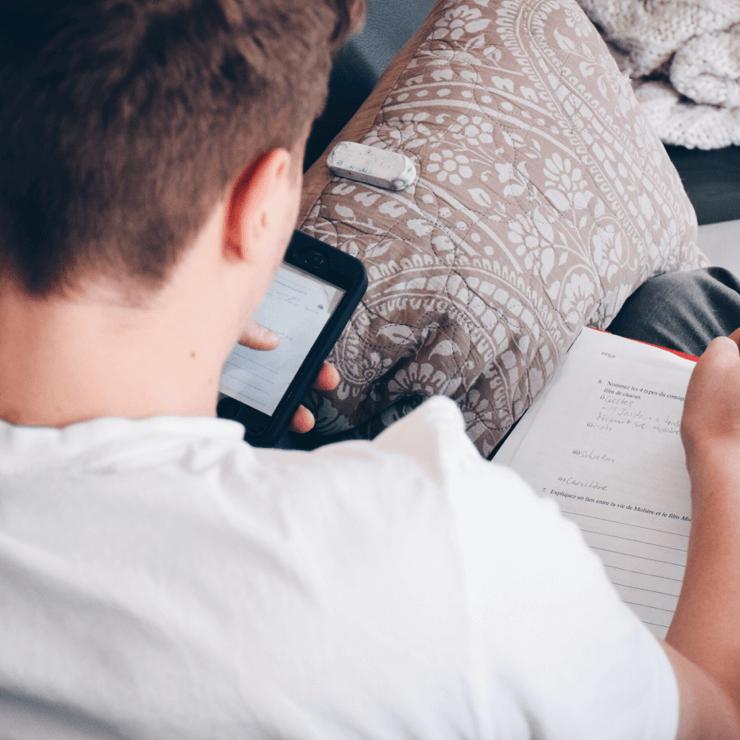 Jongen zoekt een contact op met zijn smartphone