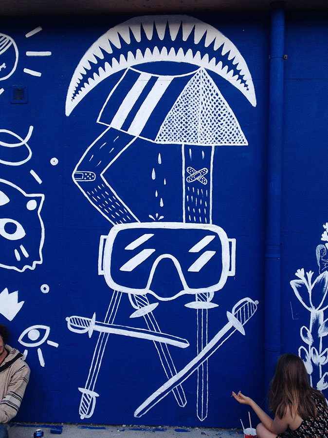 Photo of the wall painting in Geneva by Charlotte Mermoud, it is blue and white with a frown, swords, legs, and scuba mask