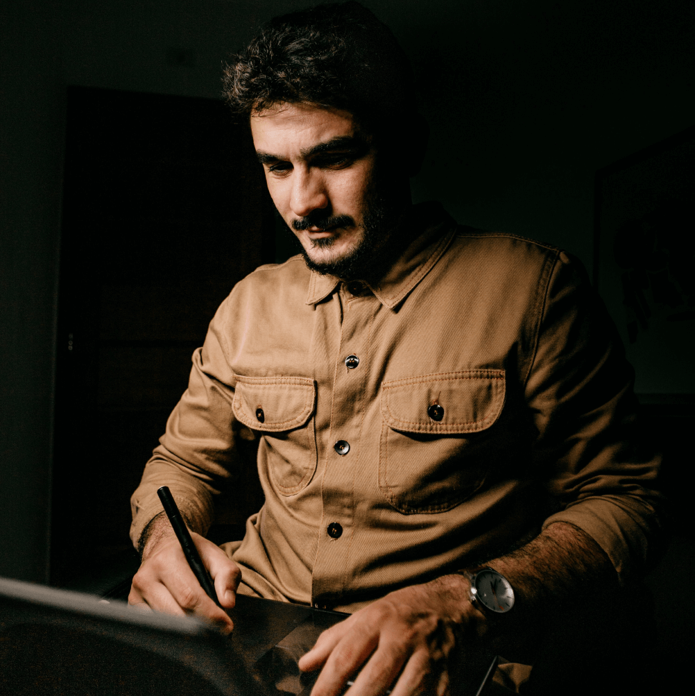 An art director wearing a brown button-up working on a tablet