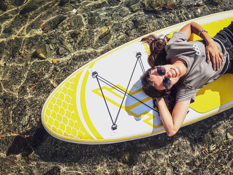 ragazza sdraiata su una tavola da sul con la maglietta grigia con stampato il logo di canottieri outdoor