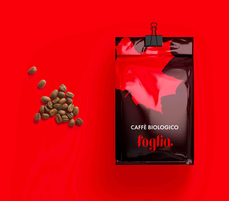 sulla destra packaging rosso di una confezione di caffè biologico con logo e brand identity di foglia, sulla sinistra chicchi di caffè sciolti su sfondo rosso acceso
