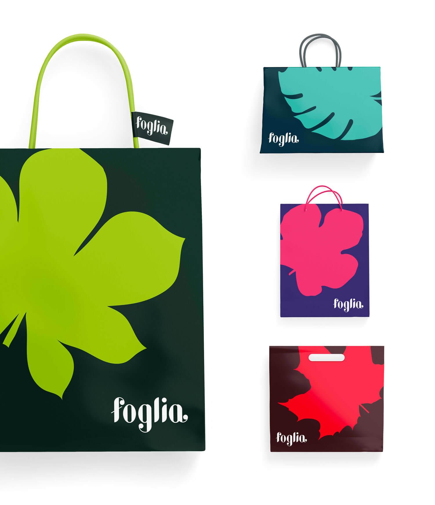 quattro sacchetti di carta con logo e brand identity di Foglia di colore verde, blu, viola e rosso su sfondo bianco