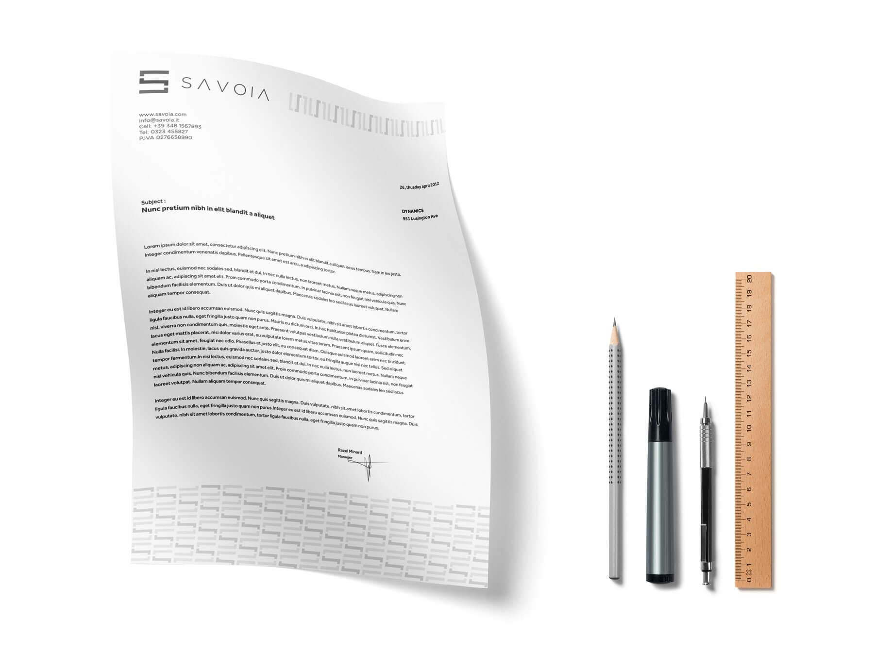 sulla sinistra carta intestata con logo e brand identity design di savoia e sulla destra tre penne e un righello. tutto su sfondo bianco.