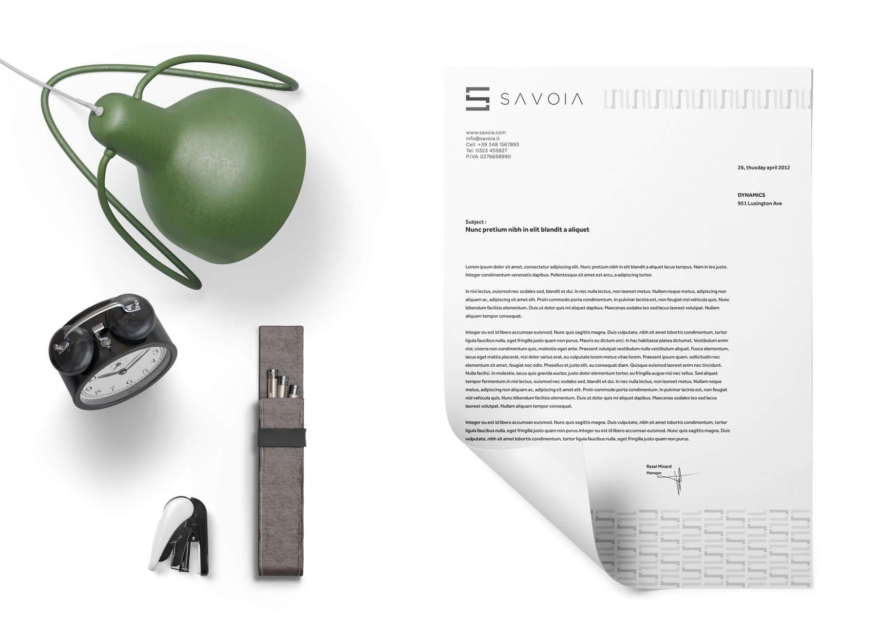 sulla sinistra c'è una lampada da studio verde, una sveglia nera e delle penne visti dall'altro. sulla destra carta intestata con logo e brand identity design di savoia di colore bianco