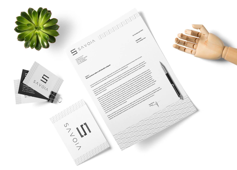 biglietti da visita, una busta e una carta intestata con logo e brand identity design di savoia visti dall'alto su sfondo bianco